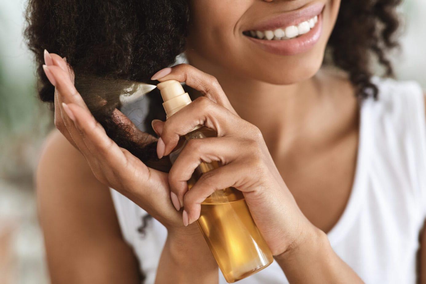 Split EAfrican Woman Applying Essential Oil Spray On Her Curly Brown hair